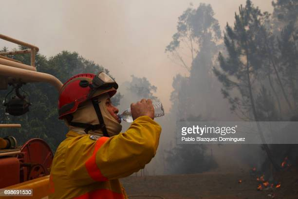 A firefighter drinks water as he works to extinguish a fire in Mega Fundeira village after a wildfire took dozens of lives on June 20 2017 near Picha...