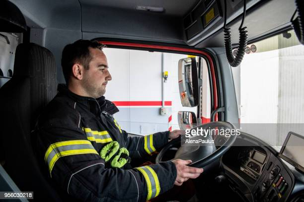 firefighter driving a fire truck - fire engine stock pictures, royalty-free photos & images