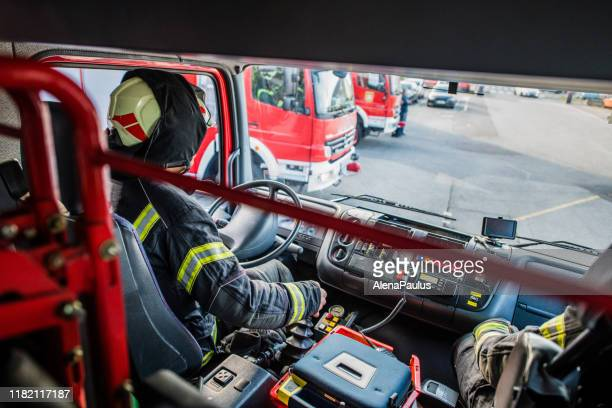 firefighter driving a fire truck top view - fire engine stock pictures, royalty-free photos & images