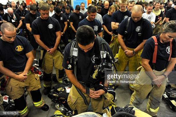 Firefighter Dustin Stevens of Franktown Fire Fire and Rescue and his fellow firefighters take a moment of silence before heading up the stairs to...