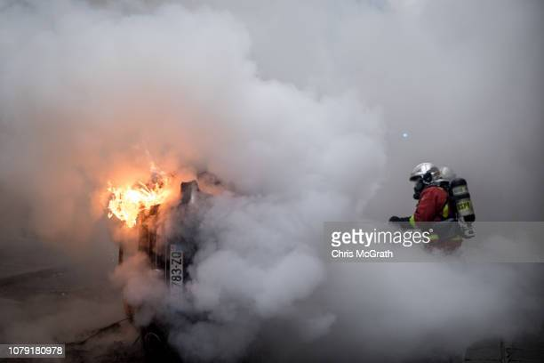 A firefighter extinguishes a burning car during the 'yellow vests' demonstration near the Arc de Triomphe on December 8 2018 in Paris France ''Yellow...