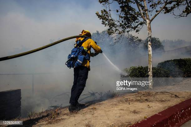 Firefighter extinguishes a fire at Northwood High School in Irvine. At about 6:47am on Monday, October 26, The Silverado Fire began as a brush fire...