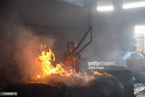 Firefighter extinguishes a fire inside the building after a fire broke out at a factory named Hashem Foods Ltd in Rupganj of Narayanganj district on...