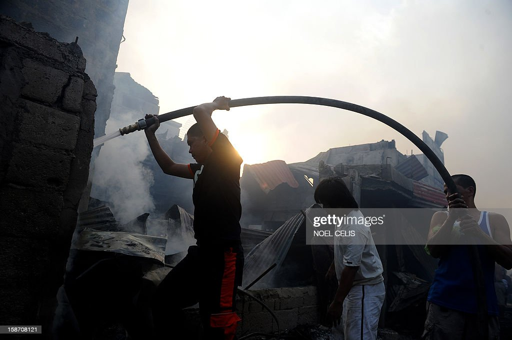 A firefighter (L) extinguishes remaining flames after a pre-dawn fire engulfed a slum area in Manila on December 25, 2012. At least seven people were killed and thousands left homeless as two fires struck the Philippine capital on Christmas Day, sparking riots as a slum went up in flames, Manila's fire marshal said.