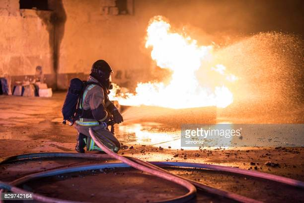 firefighter extinguishing fire - fire protection suit stock photos and pictures