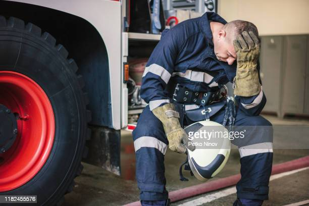 firefighter feeling depressed - fire protection suit stock pictures, royalty-free photos & images