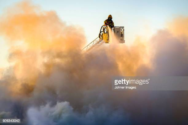 firefighter fighting fire - rescue services occupation stock photos and pictures