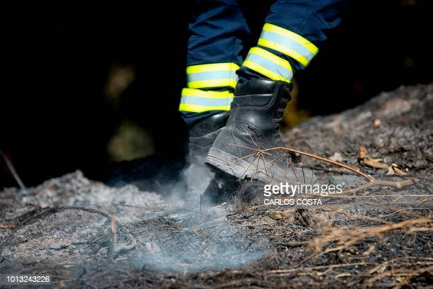 Firefighter fights a wildfire near Monchique in the Portuguese Algarve, on August 8, 2018. - Spain and Portugal approached record temperatures at the...