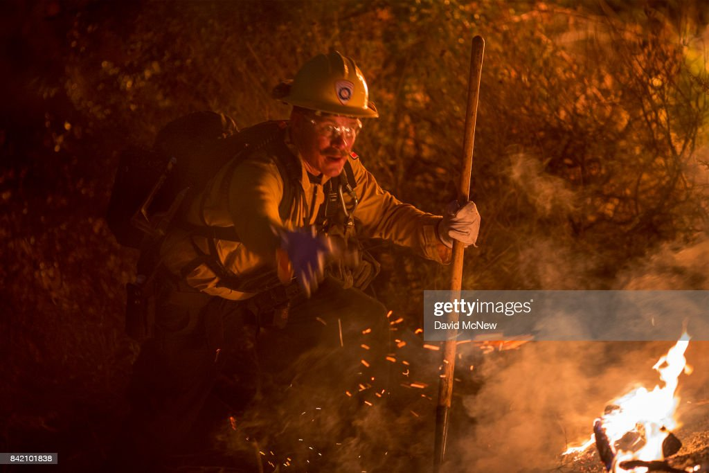 A firefighter fights flames in chaparral brush using only a hand tool at the La Tuna Fire on September 2, 2017 near Burbank, California. Los Angeles Mayor Eric Garcetti said at a news conference that officials believe the fire, which is at 5,000 acres and growing, is the largest fire ever in L.A. People have been evacuated from hundreds of homes in Sun Valley, Burbank and Glendale. About 100 Los Angles firefighters are expected to return soon from Texas, where they've been helping survivors from Hurricane Harvey.