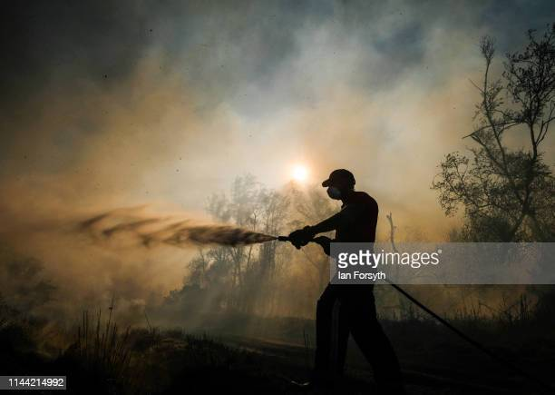 A firefighter from Cleveland Fire Brigade tackles a woodland fire in the hills above Guisborough on April 21 2019 in Guisborough England The cause of...
