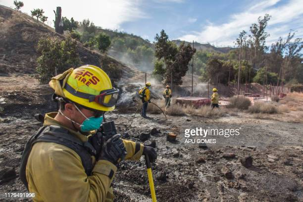 A firefighter from Santa Fe Springs talks on the radio while he battles to control hotspots of the Maria Fire in Santa Paula Ventura County...