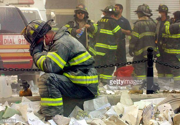 Firefighter Gerard McGibbon, of Engine 283 in Brownsville, Brooklyn, prays after the World Trade Center buildings collapsed September 11, 2001 after...