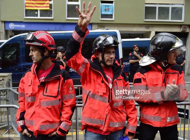 A firefighter gestures as they stand between demonstrators and the Catalan Popular Party headquarters during a protest called by CNT union during a...