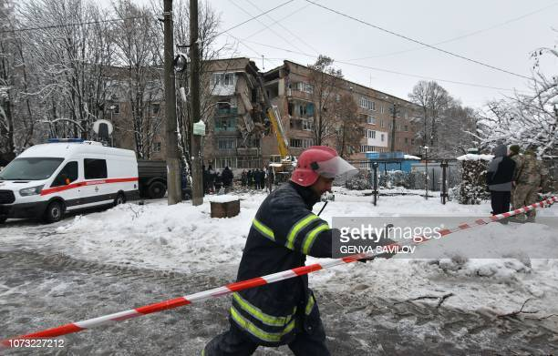 A firefighter gestures with a partially destroyed fivestorey building in background on the site of a gas explosion in the town of Fastiv on December...