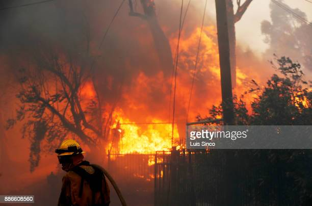 A firefighter gets into position to battle the Creek Fire as a house is engulfed in flames near the intersection of Johanna Avenue and McBroom Street...