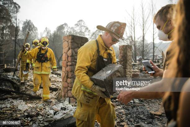 Firefighter hands a safe to Julian and Lisa Corwin in the Fountaingrove neighborhood on October 13, 2017 in Santa Rosa, California. Corwin is part of...