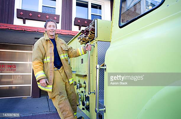firefighter hangs on to side of fire truck