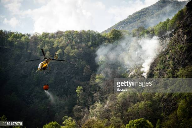 firefighter helicopter putting out a fire on mountain forest - environmental damage stock pictures, royalty-free photos & images
