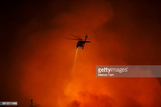 A firefighter helicopter shines a spotlight onto an area before making a water drop on the Blue Cut fire that is burning north of the Lyle Creek...