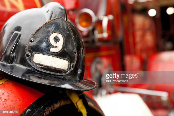 firefighter helmet resting on firetruck - firetruck stock photos and pictures