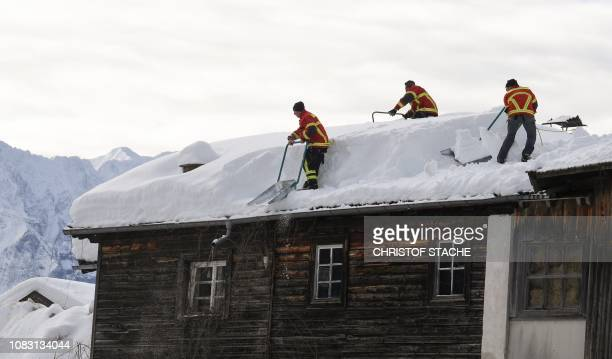 Firefighter help removing snow from a rooftop in the small Bavarian village of Kruen near Garmisch-Partenkirchen, southern Germany, on January 15,...
