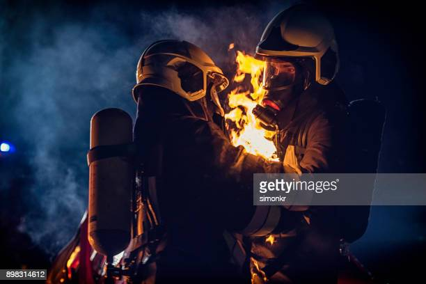firefighter helping another fireman - fire protection suit stock photos and pictures