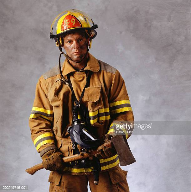 Fire-fighter holding axe, (Portrait)