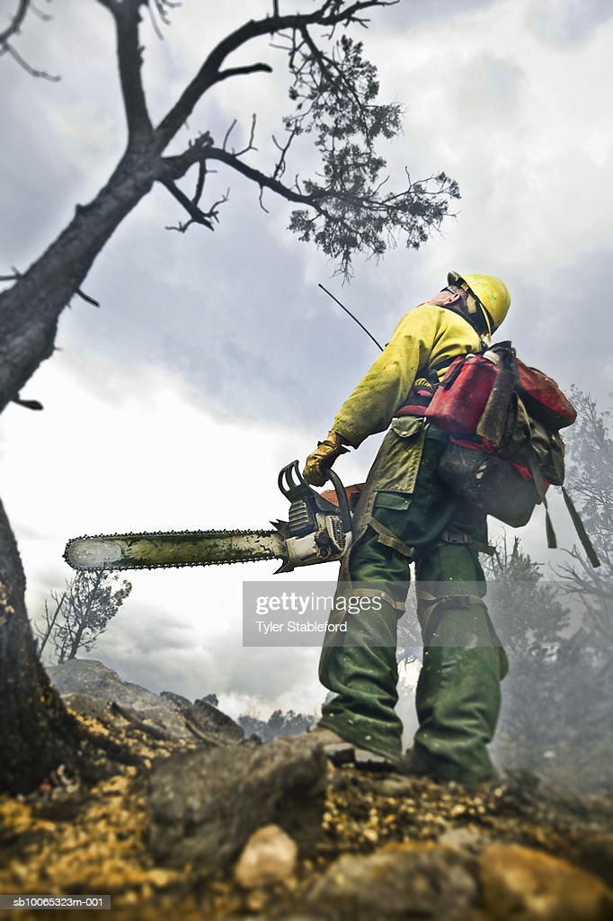 Fire-fighter holding chainsaw while working : Foto stock