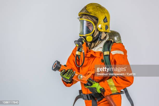 firefighter holding fire hose against white background - fire protection suit - fotografias e filmes do acervo