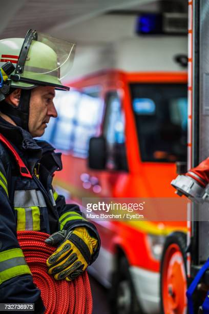 Firefighter Holding Hose At Fire Station