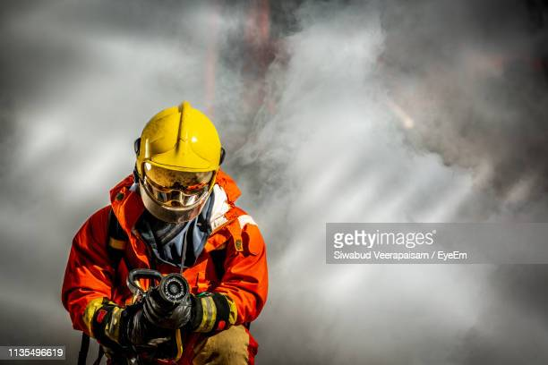 firefighter holding hose - fire protection suit - fotografias e filmes do acervo
