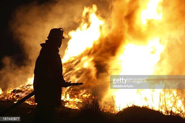 firefighter holding hose pointing water stream onto fire - firefighter stock pictures, royalty-free photos & images
