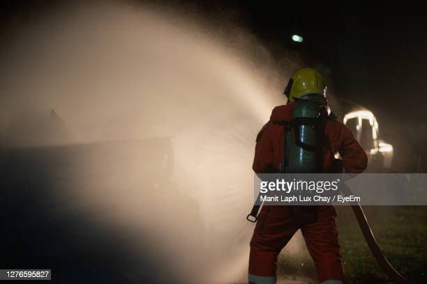 firefighter holding pipe at night - one man only stock pictures, royalty-free photos & images