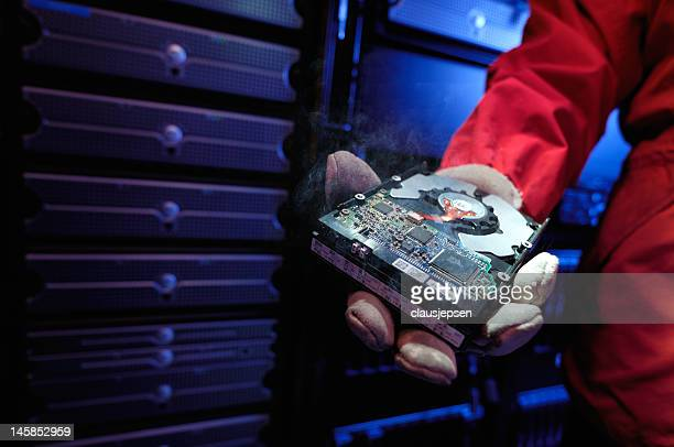 Firefighter holding smoking computer hard drive