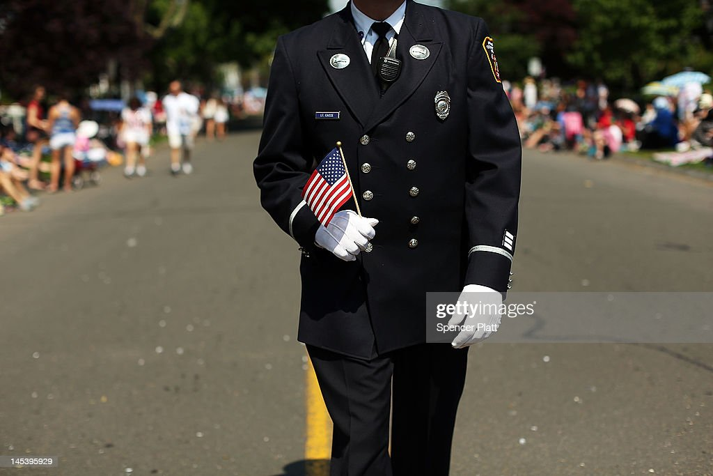 A firefighter holds a falg as he walks in the annual Memorial Day parade on May 28, 2012 in Fairfield, Connecticut. Across America towns and cities will be celebrating veterans of the United States Armed Forces and the sacrifices they have made. Memorial Day is a federal holiday in America and has been celebrated since the end of the Civil War.