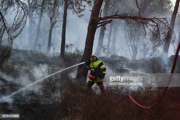 A firefighter holds a hose as he works to extinguish a fire in PortdeBouc southeastern France on August 10 2017 Dry conditions fuelled a wildfire on...