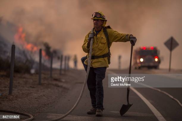 A firefighter holds a hose on the 120 freeway during the La Tuna Fire on September 2 2017 near Burbank California Los Angeles Mayor Eric Garcetti...