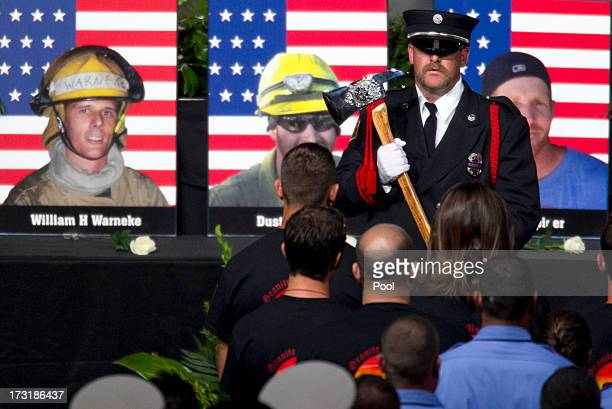 A firefighter holds an axe during the processional during a memorial service honoring 19 fallen firefighters at Tim's Toyota Center July 9 2013 in...