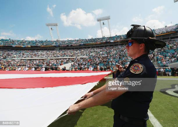 A firefighter holds the American flag on the field prior to the start of the game between the Tennessee Titans and the Jacksonville Jaguars at...