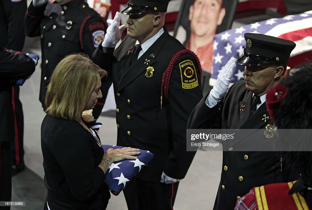 A firefighter honor guard present American flags to the family members of the twelve fallen volunteer firefighters at the West memorial service at Baylor University on April 25, 2013 in Waco, Texas. The memorial service honored the volunteer firefighters that lost their lives at the fertilizer plant explosion in West, Texas last week.
