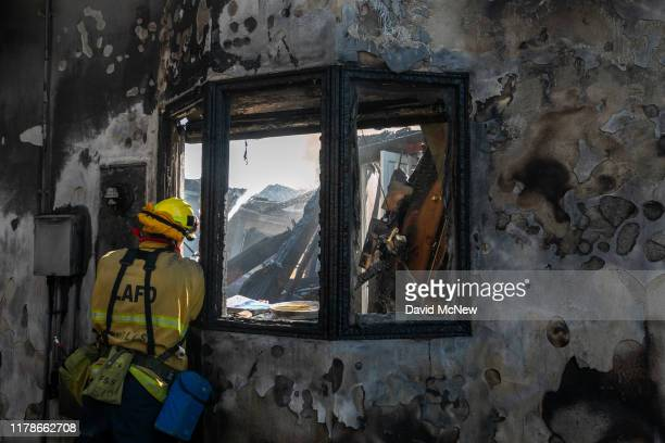 A firefighter hoses down a burning house during the Getty Fire on October 28 2019 in Los Angeles California Reported at 130 am the fire quickly...