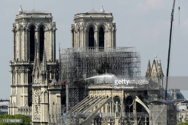 A firefighter hoses down a section of NotreDame Cathedral following a major fire on Monday on April 17 2019 in Paris France A fire broke out on...
