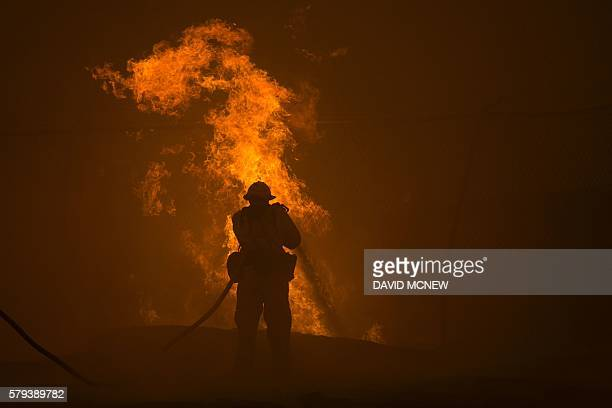 TOPSHOT A firefighter hoses down burning pipes near a water tank at the Sand Fire on July 23 2016 near Santa Clarita California Fueled by...