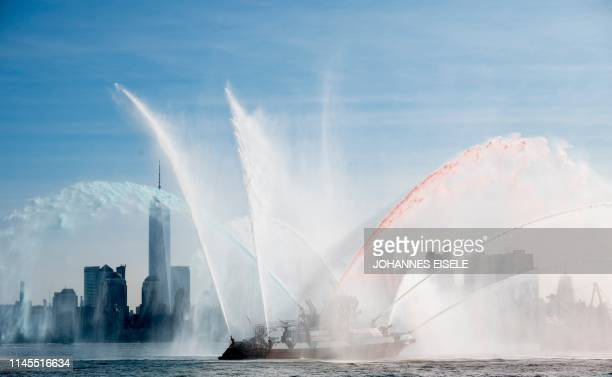 Firefighter II from the Fire Department of New York sprays water to salute the Fleet Week parade on May 22 2019 in New York