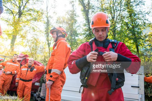 firefighter in a dry suit preparing for the rescue operation by the river - guarding stock photos and pictures