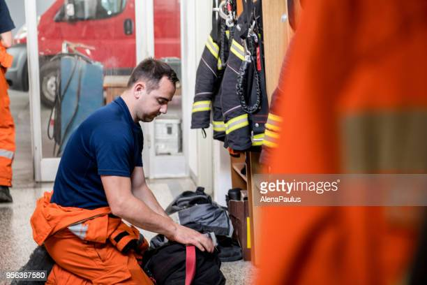 firefighter in a locker room - fire station stock photos and pictures