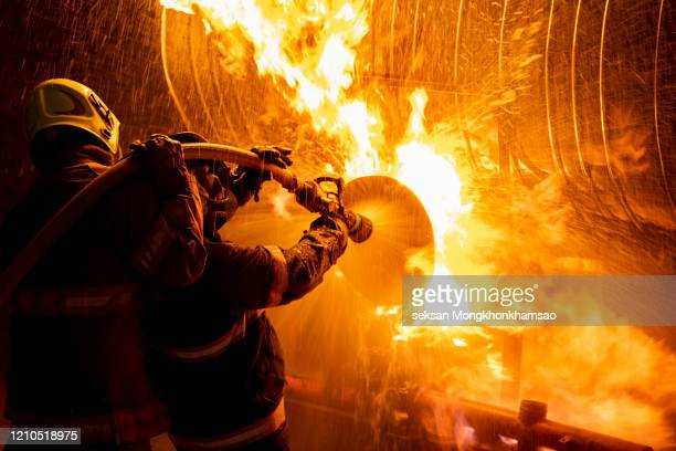 firefighter in fire fighting suit spraying water, firemen fighting raging fire with huge flames of burning, fire prevention and extinguishing concept - firefighter stock pictures, royalty-free photos & images