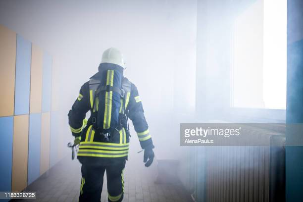firefighter in fire-rescue operation - in flames i the mask stock pictures, royalty-free photos & images