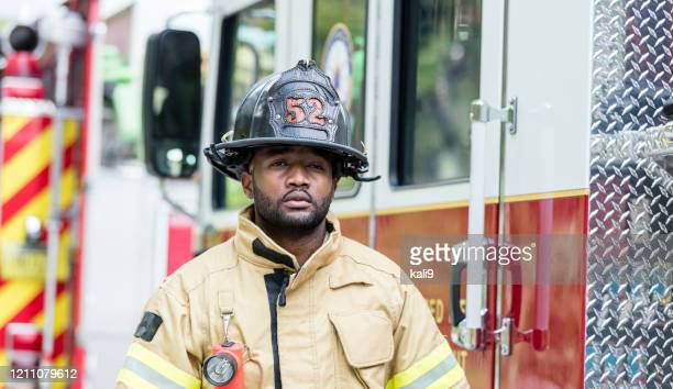 firefighter in protective clothing outside fire truck - firefighter stock pictures, royalty-free photos & images