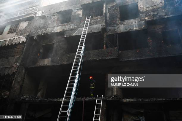 A firefighter inspects a burnt building after a fire broke out in Dhaka on February 21 2019 At least 69 people have died in a huge blaze that tore...